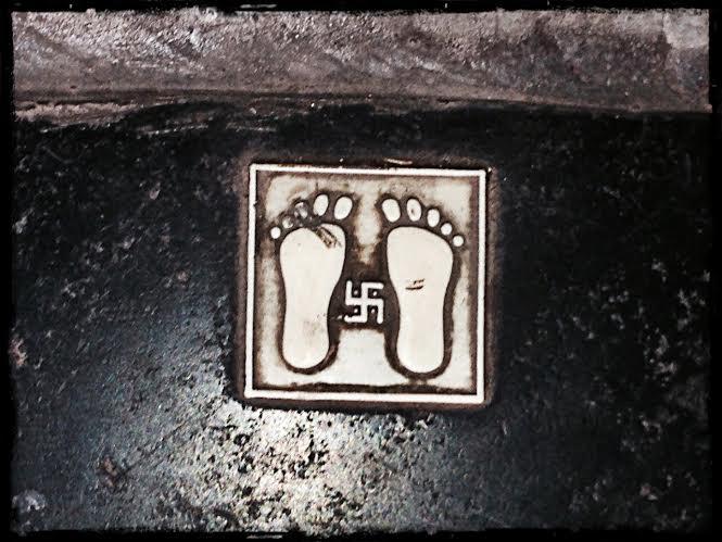Vid de flesta kommerciella trösklar finns de här bara fötterna med soltecknet i mitten. Soltecknet lär betyda välstånd och tecknet uppmanar besökare att ta av sig skorna.