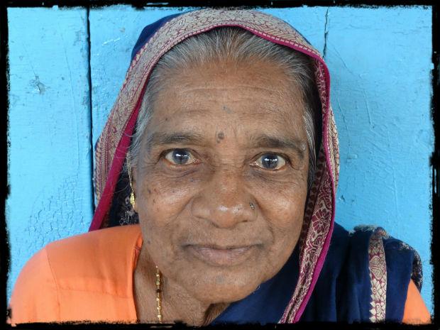 Kvinna vid sitt blåa hus L